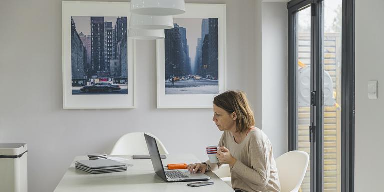 person sitting at table in home working on laptop while drinking coffee