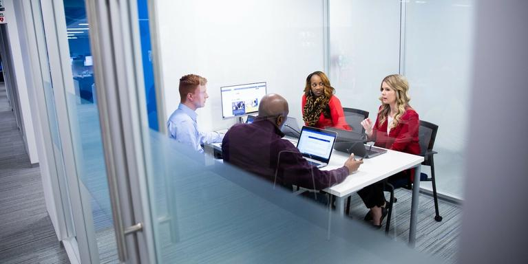 four people sitting at a table in a conference room