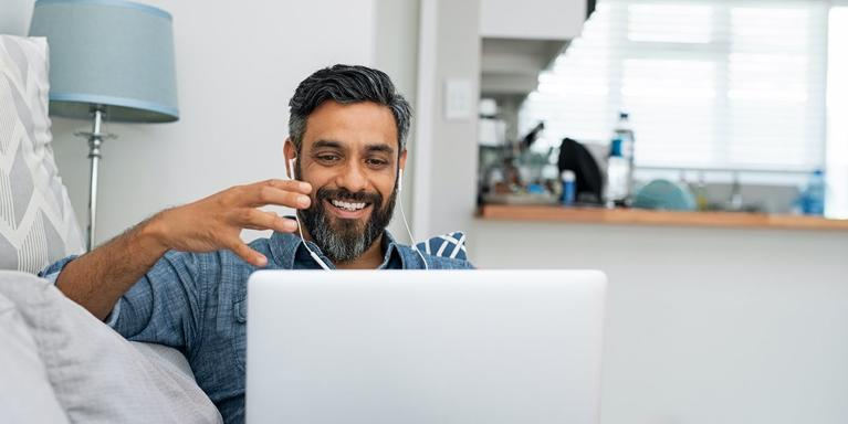 person sitting on a couch doing a video call on a computer