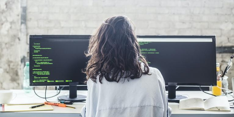 person sitting in front of two computer screens and writing code