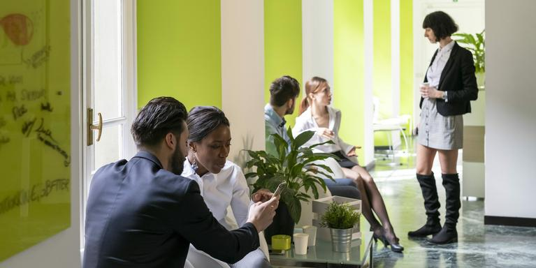 group of coworkers talking in the public area of an office