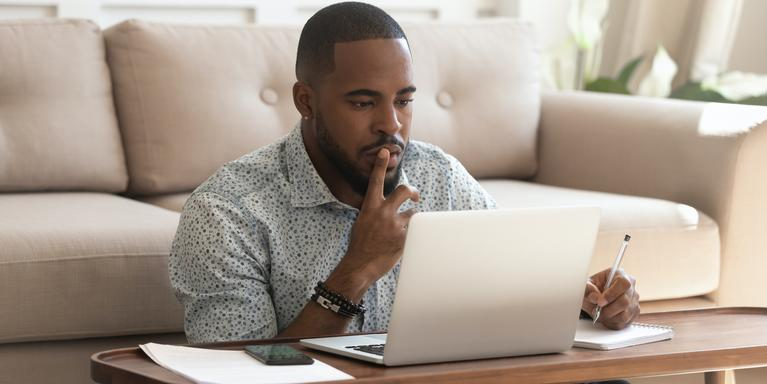 person sitting on floor in front of coffee table with laptop