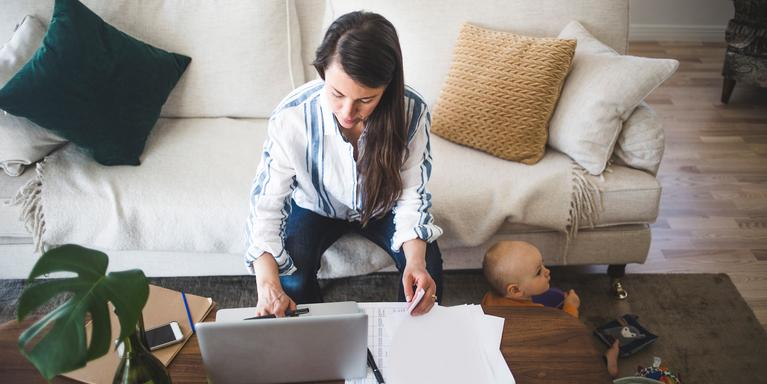 person sitting on couch, working at coffee table looking at papers and laptop while toddler sits on the floor