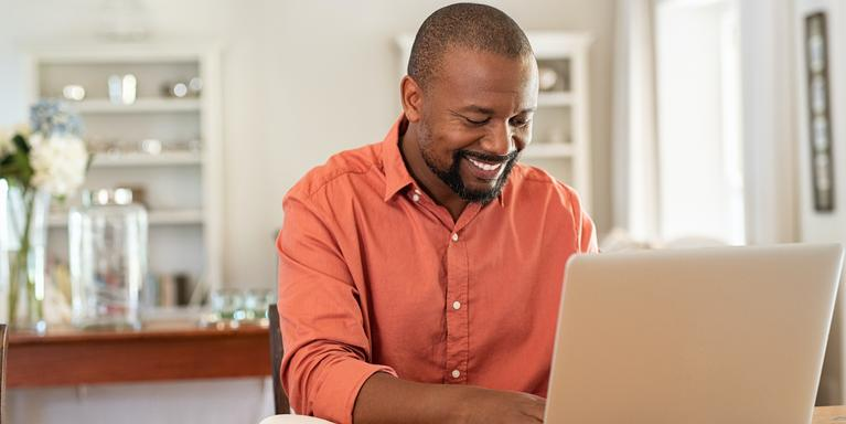 person sitting at counter working on laptop