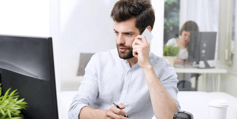 person sitting at desk, talking on the phone in front of a computer with another person visible in the background in another office