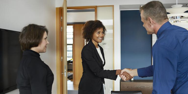 two people shaking hands in office with third person watching