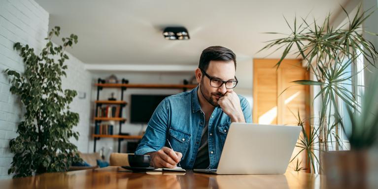 man at table looking at laptop while writing