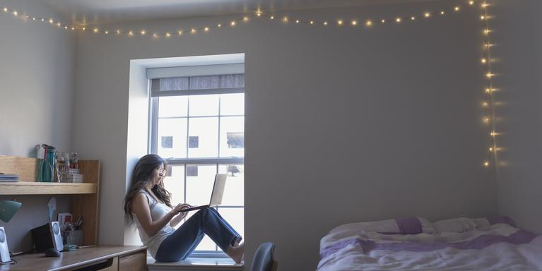 person sitting on windowsill in dorm room working on laptop