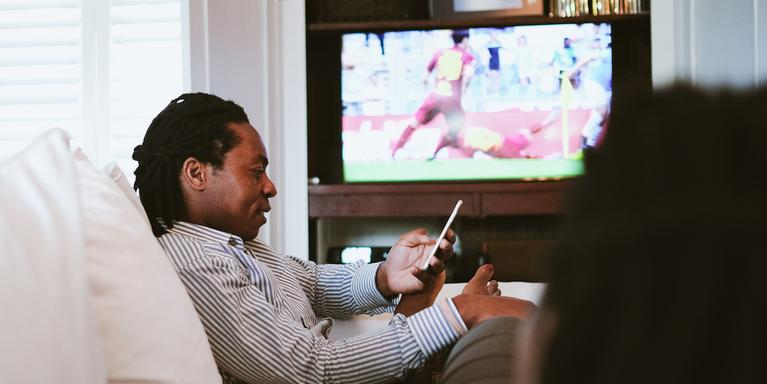 person watching a soccer game on TV and looking at their phone