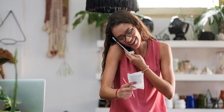 smiling person on the phone and holding receipts
