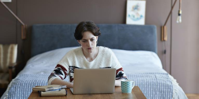 person on laptop in front of bed
