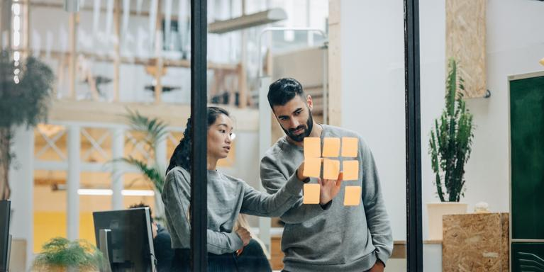 two people looking at sticky notes on a glass wall