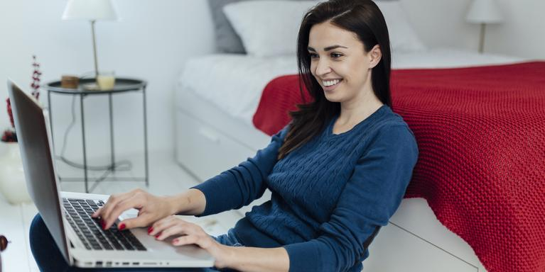 smiling person sitting on floor next to bed on laptop