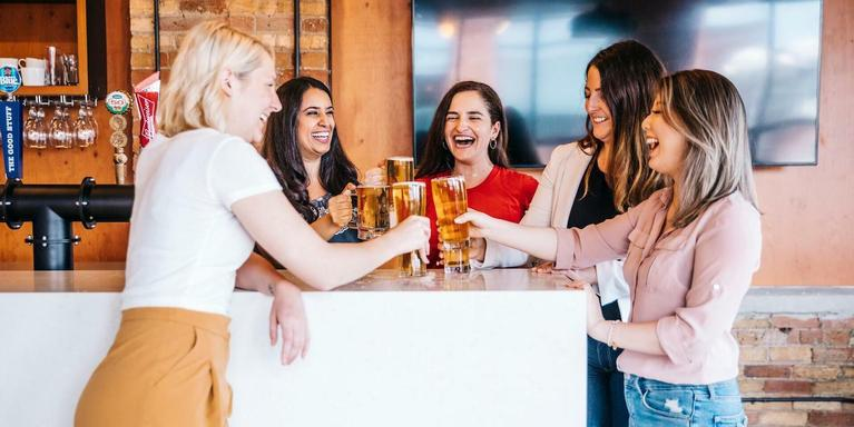 a group of people gathered around an office bar, clinking beer glasses