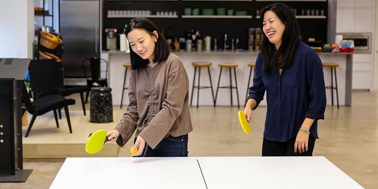 employees playing ping pong in an open plan office