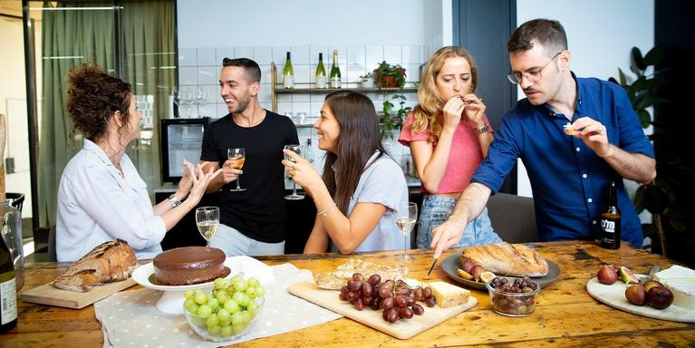 Employees gathered around a communal table eating snacks