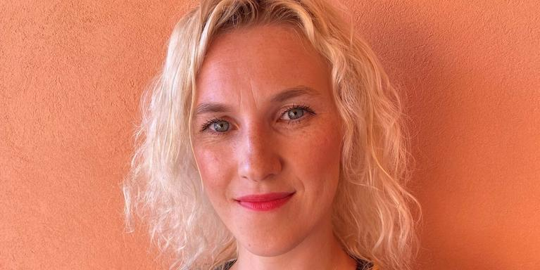 person with short blond wavy hair and blue eyes in front of an orange wall
