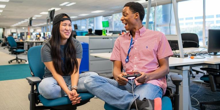 two employees laughing while playing video games in an office