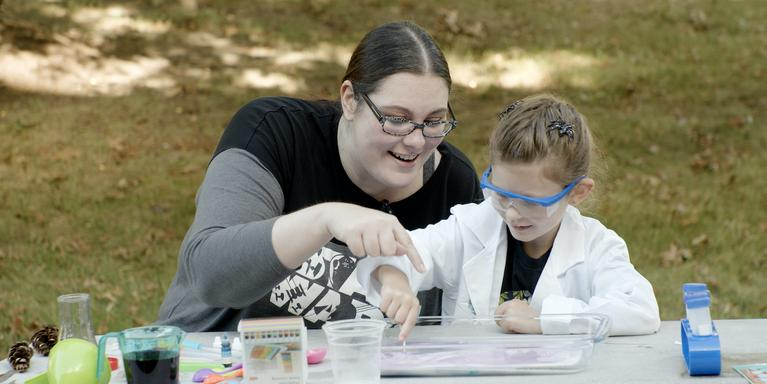 a person and a child sitting at a table outside doing a science project