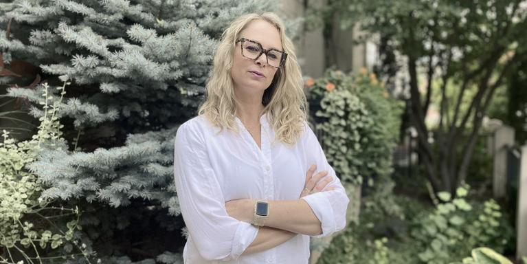 person with long blonde hair and black-framed glasses standing in front of trees