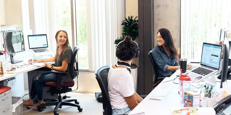 three people chatting from their desks ini an open plan office