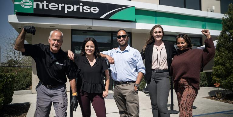 group of five employees standing in front of an Enterprise branch in Valencia, CA