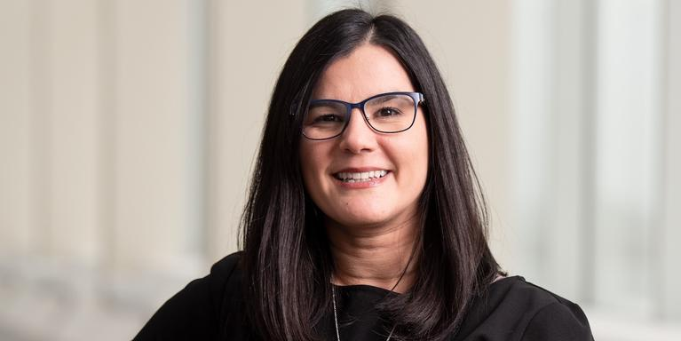 person with long dark hair and glasses