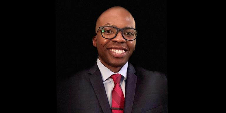 smiling person wearing glasses and a suit with a red tie
