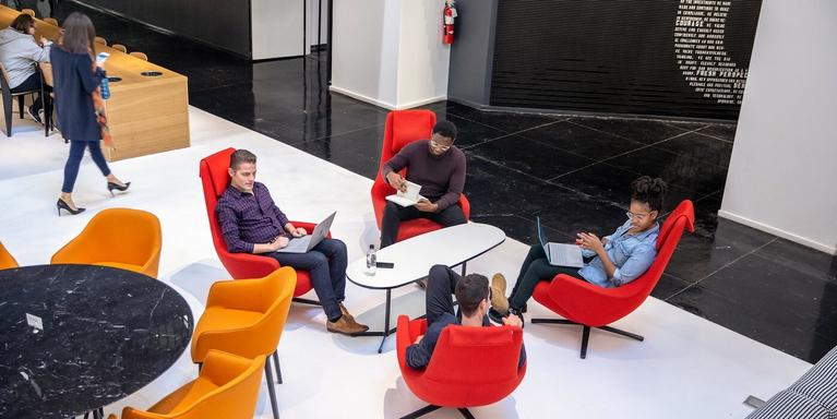 employees sitting around a coffee table in an office
