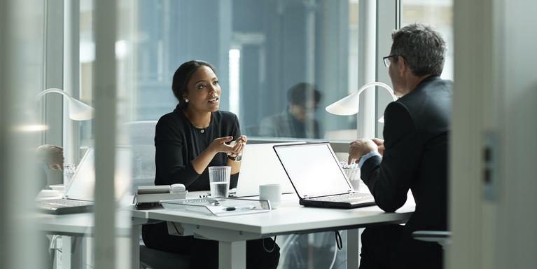 two people in an office talking across a desk