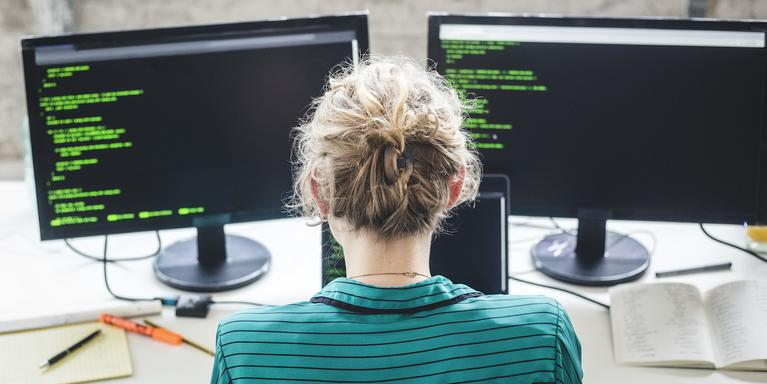 High angle view of engineer looking at code on a double-monitor desktop computer