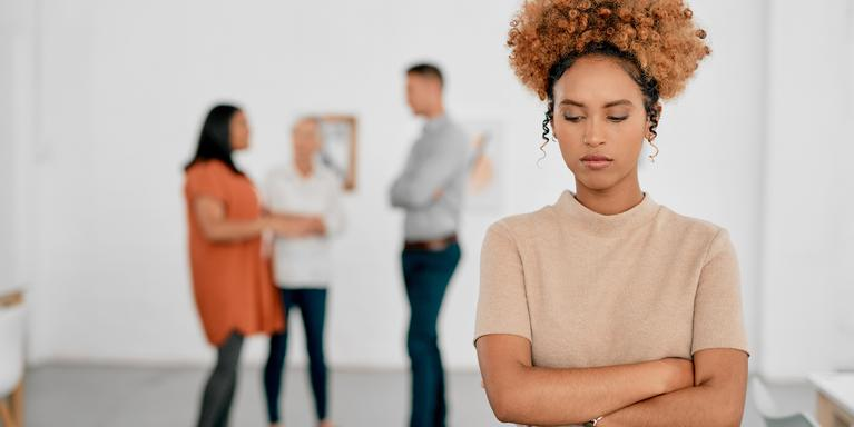 sad person standing with arms crossed with group of coworkers in the background