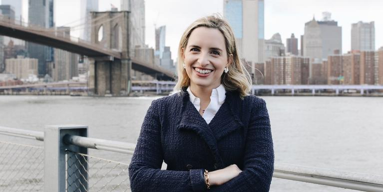 person with blonde hair smiling in front of the Brooklyn Bridge