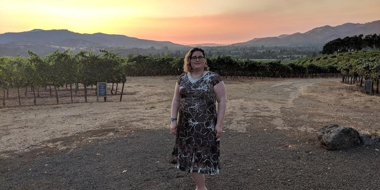 person smiling and standing in front of a vineyard during sunset