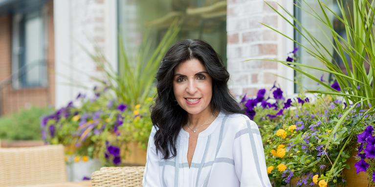 person with long black hair sitting in a garden