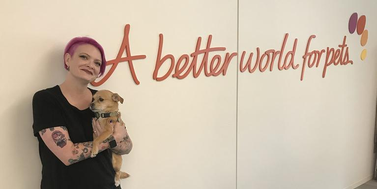 "person with short pink hair holding a dog and standing against a wall that says ""A better world for pets."""
