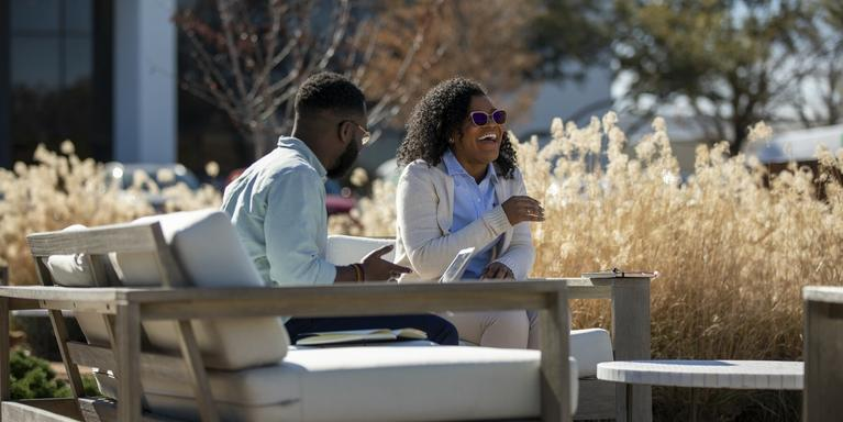 two people chatting while sitting on patio furniture outside an office building