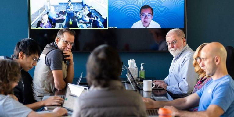 people meeting in a conference room with other remote employees