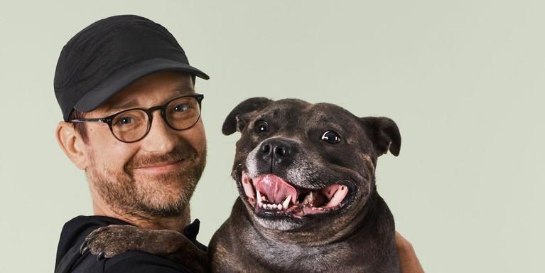 person wearing a black baseball cap and holding a dog