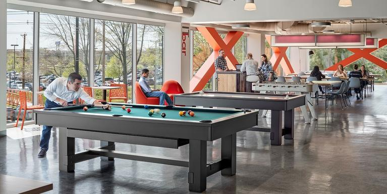 employees playing pool in an open-plan office