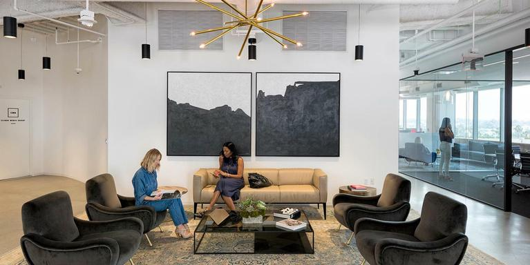 Two people sitting on couches in an office lounge area