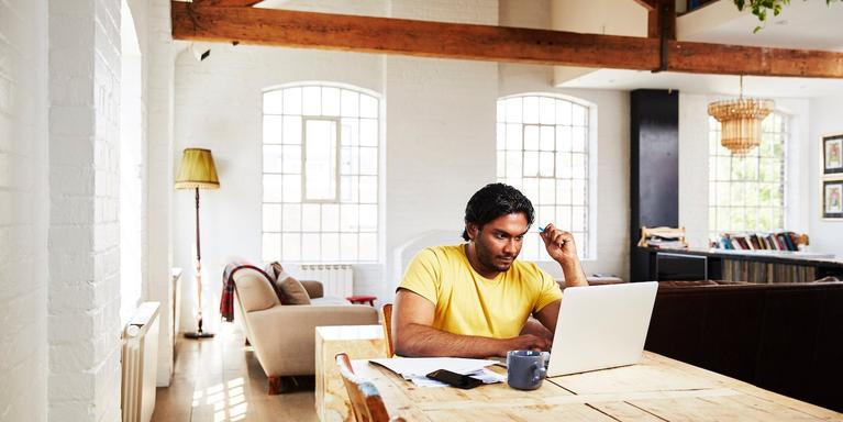 person sitting at a dining table at home working on a laptop