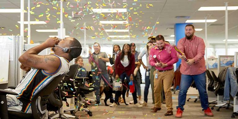 employees celebrating inside the office with confetti