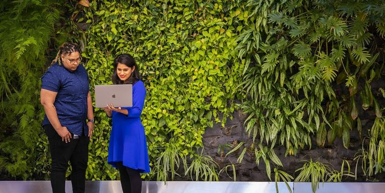 two people standing in front of a plant-covered wall, looking at a laptop together