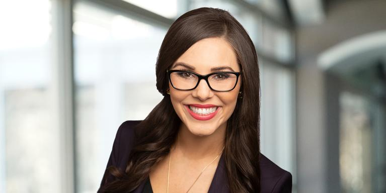 smiling person with long brown hair and glasses
