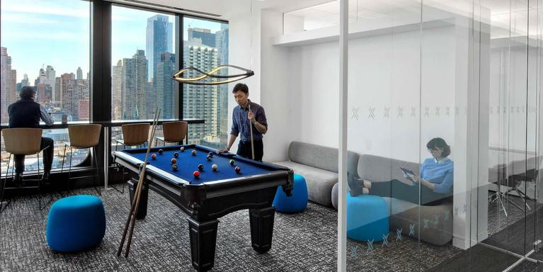 employees hanging out in an office lounge area with a couch, a pool table, and city skyline views