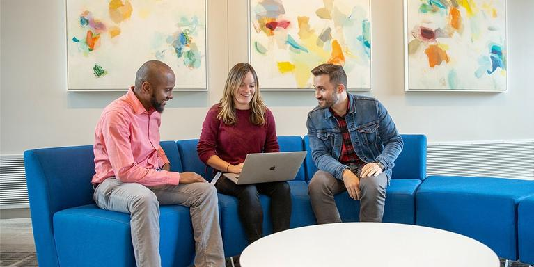 three employees gathered in front of a laptop at the office.