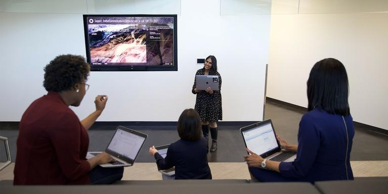 employee giving a presentation in front of three people