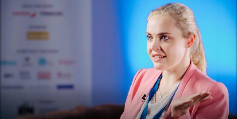 person with blonde hair in a ponytail wearing a pink blazer in front of a blue screen