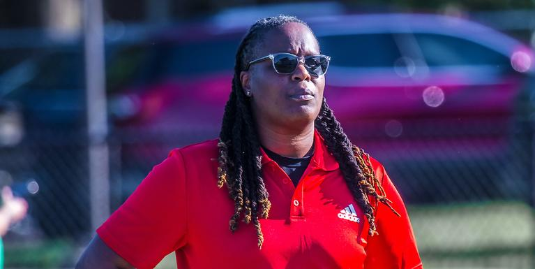 person with braids and sunglasses wearing a red polo shirt